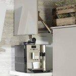 """Raffinierte Stauraumlösung: Der Kaffeevollautomat """"parkt"""" hinter einer grifflosen Lifttür, bis er zum Einsatz kommt. An der Design-Schräghaube kann man sich den Kopf nie mehr anstoßen. (Foto: AMK)"""