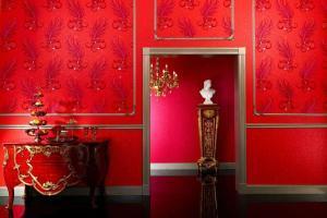 """Luxus pur - rote Tapete mit goldenen Strahlenornamenten (""""Glööckler Deux"""" von Marburg).Foto: djd/Deutsches Tapeteninstitut"""