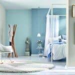 """Im Bett liegen und von einem entspannten Tag am Meer träumen - Blau- und Aquatöne versprühen Urlaubsfeeling pur. Zum Beispiel """"Wallton"""" von Rasch. Foto: djd/Deutsches Tapeten-Institut GmbH"""