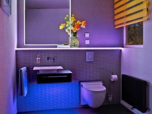 Mithilfe eines Bluetooth-Receivers lassen sich die farbigen LED-Module ganz bequem per App mit dem Smartphone oder Tablet steuern. Foto: djd/Schlüter-Systems