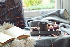 Das gemütliche Haus mit einer Tasse Tee, Decke, Buch und Kerzen genießen - so ist der Hygge Stil Foto: Von topotishka / shutterstock.com