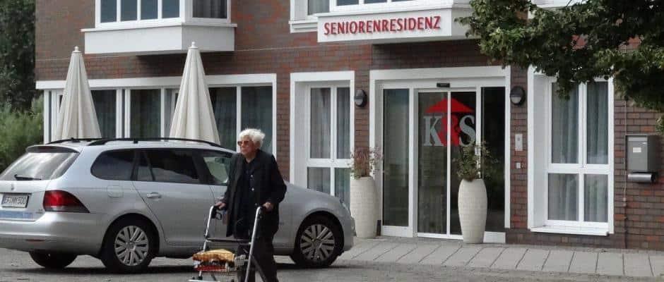 Ältere Frau vor einer Seniorenresidenz