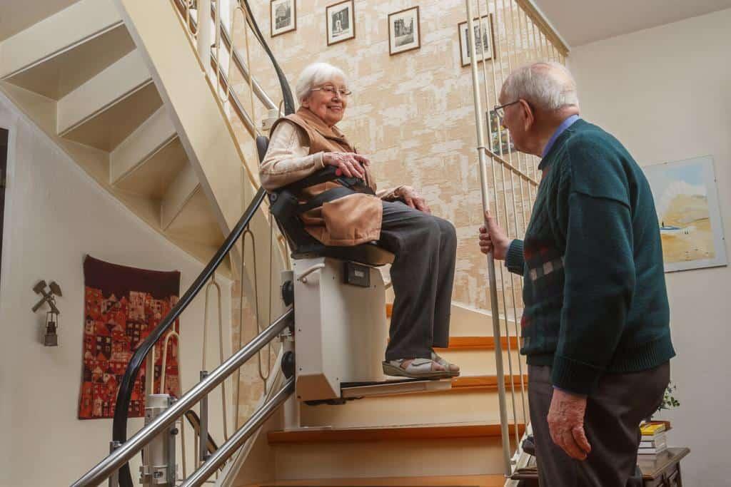 Älteres Paar an einer Treppe mit Treppenlift