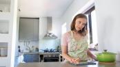 Junge Frau kocht in einer Miniküche